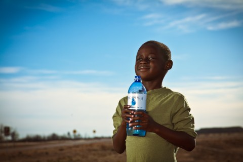 still from video shoot of young boy, smiling, holding bottle of water