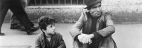 From A Bicycle Thief: boy and father look abjectly off screen while sitting on a dirty street curb
