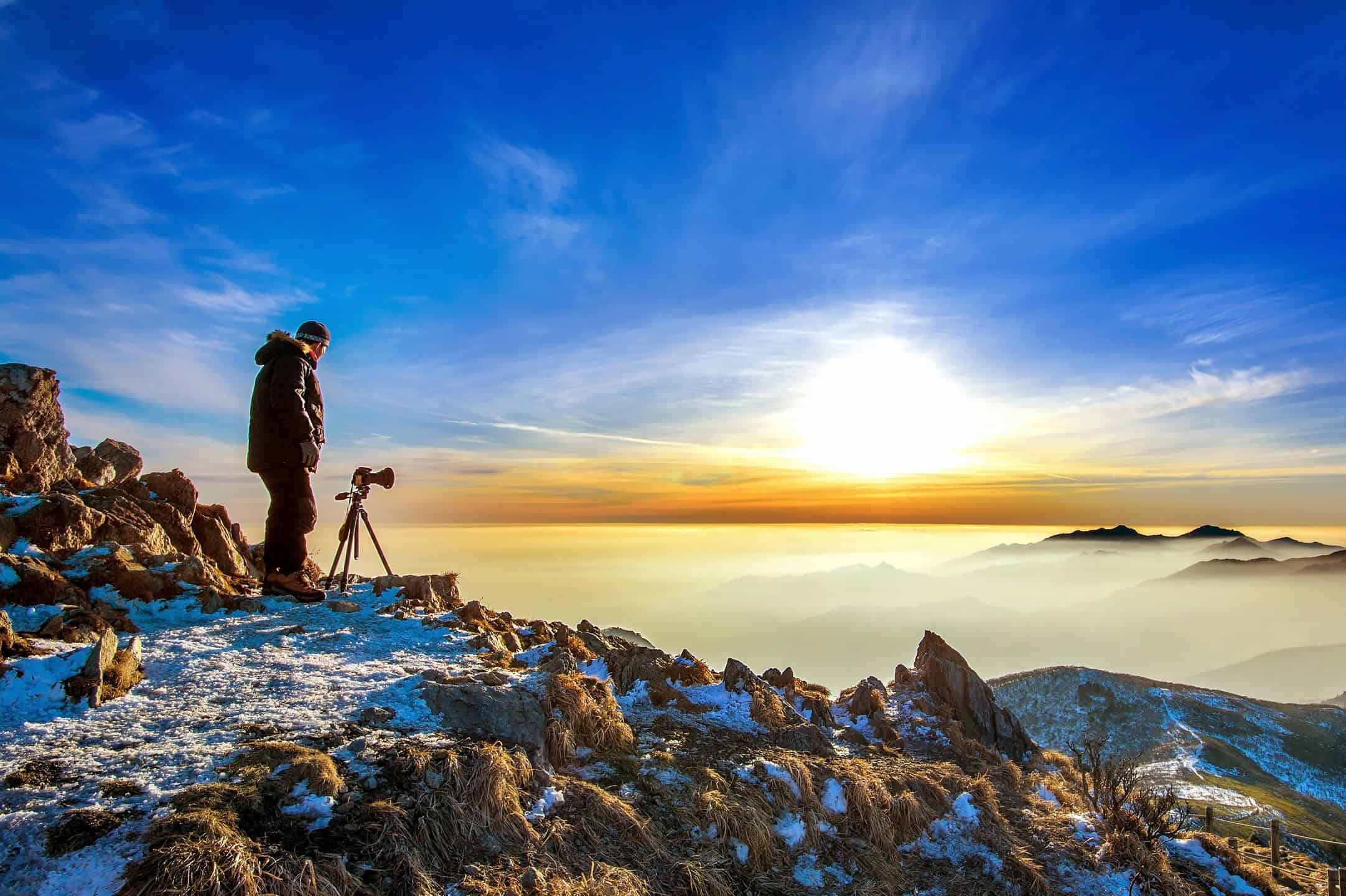 man photographs valley at sunrise