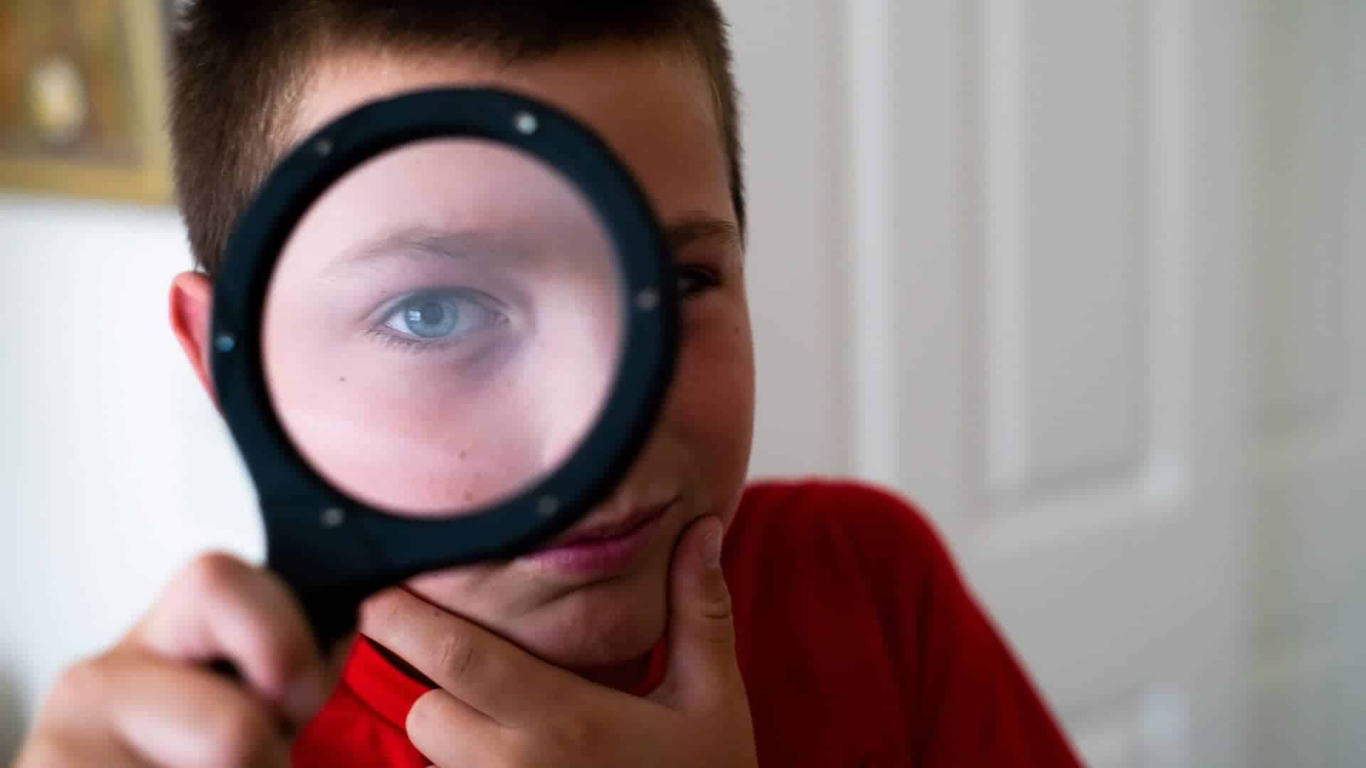 still of boy looking through looking glass